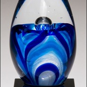 1633-  Art glass egg with blue and white accents on black glass base